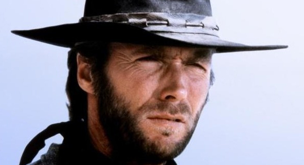 Clint Eastwood wearing a cowboy hat in a Western movie while squinting